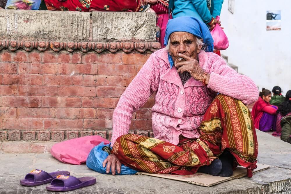 stara kobieta z suchą skórą paląca papierosa na ziemi